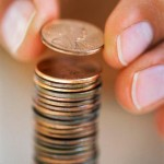 Fingers Holding Penny Above Stack of Pennies